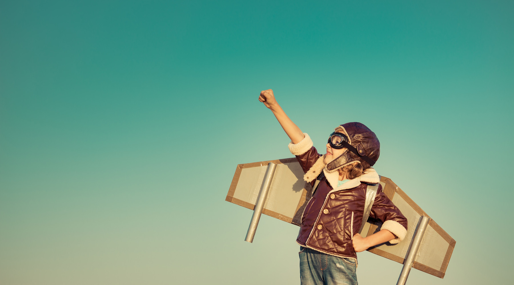 Kid pilot with toy jet pack against autumn sky background. Happy child playing outdoors